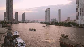 Sunset at Chao Phraya river with a view of boats and skyscraper