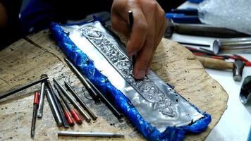 artesão usando ferramenta entalhando padrão tailandês em placa de metal