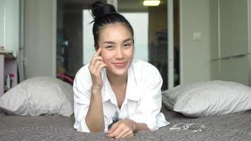 Mujer asiática sonríe y muestra su rostro en la cama en casa