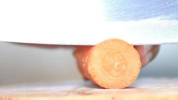 Manos cortando una zanahoria en una tabla de madera