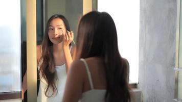 mulher asiática checando o rosto no espelho