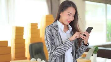 Mulher de negócios asiática usando telefone celular inteligente video