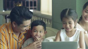 Happy Asian family watching to laptop.