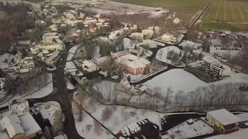 Drone orbiting a snowy castle in a village in 4K