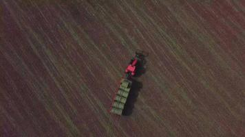Aerial top down drone view of a red tractor on a field in 4K video
