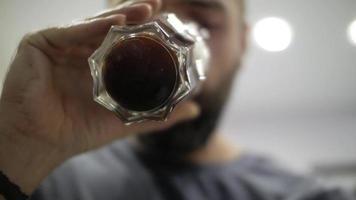 homem tomando café com um copo transparente