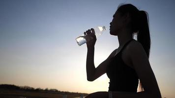 Woman holding bottle up to drink water after exercise