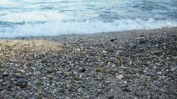 ondas quebrando em uma praia com pequenas pedras