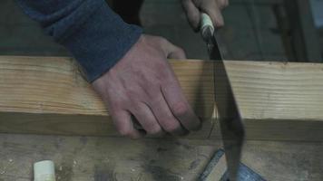 hombre aserrando una viga de madera
