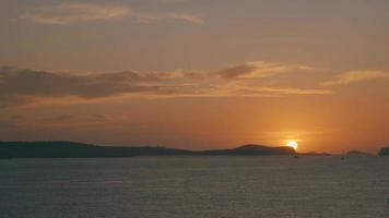 Ibiza Sonnenuntergang hinter einem Berg am Meer