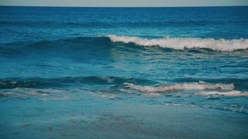 Teal sea waves breaking on the beach video