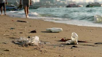La gente camina en la playa con desechos plásticos. video