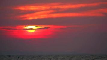 puesta de sol detrás de una nube junto al mar