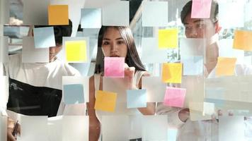 Businesspeople discussing ideas with post-its on a glass wall video
