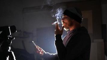 homem barbudo fuma e olha para o telefone
