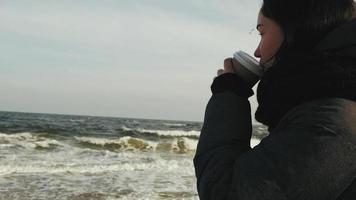 mujer bebe cafe cerca del mar