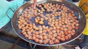 pessoas fritando bolinhos de peixe em óleo quente