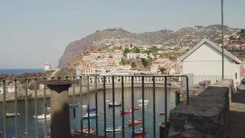 Overlooking a small fishing town with houses and boats in Madeira, Portugal. video