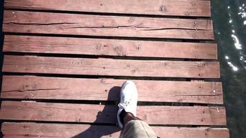 hombre caminando sobre las tablas del muelle video