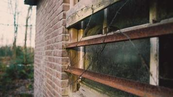 Barbed wires and metal bars covering an old window