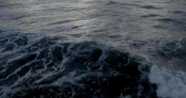 voando sobre as ondas do oceano aberto em um pôr do sol nublado video