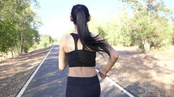 The back of a woman running at a park