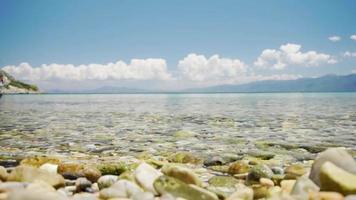 a água calma do mar batendo nas pequenas pedras na praia. video