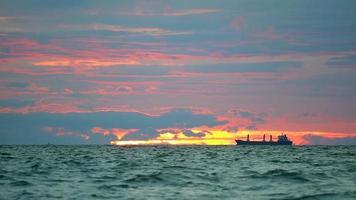 Estacionamiento de buques de carga en el mar y una nube roja oscura en el cielo del atardecer video