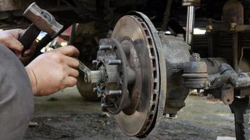 técnico que quita el cubo de la rueda delantera derecha del automóvil. video