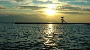 el mar y el muelle durante la puesta de sol.