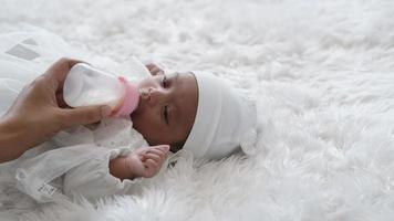 bebê recém-nascido bebe leite de uma mamadeira