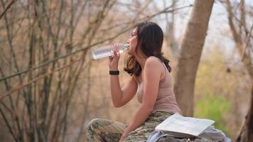 Asian Woman Drinking Water in The Forest