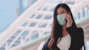 La empresaria hablando por un teléfono móvil mientras usa una máscara