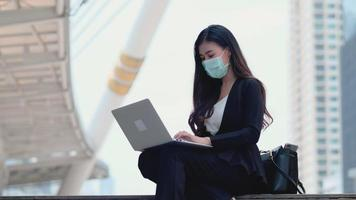 Businesswoman Wearing a Mask Uses a Laptop Outdoors video