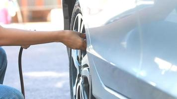 Woman's Hands Inflating a Car Tire