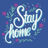 Quédate en casa letras a mano con decoración floral.