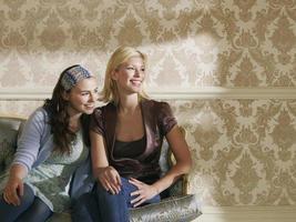 Two Smiling Women Sitting On Sofa