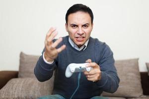 Angry man playing videogames on his sofa photo