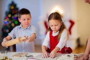 niños horneando galletas de navidad foto