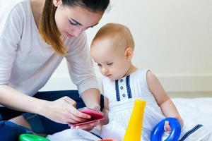 madre e hija usando un teléfono inteligente en casa foto