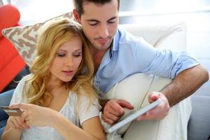 pareja en casa comprando en línea fácilmente con tableta digital