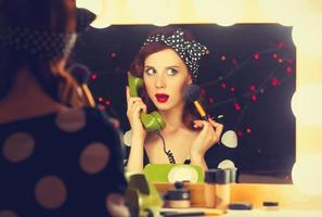 woman with dial phone applying cosmetics photo