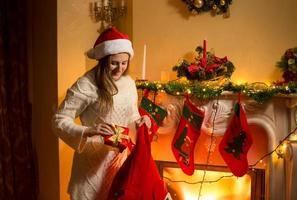 joven madre poniendo regalos de navidad en medias colgando de abeto