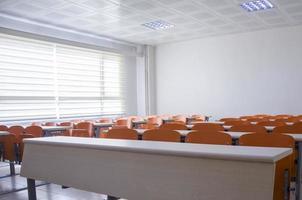 aula vacía con mesas y sillas naranjas foto