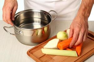 Adding vegetables into saucepan. Making vegetables bouillon.