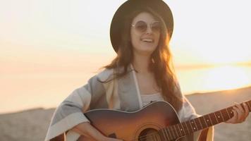 Zeitlupe. schönes Mädchen, das die Gitarre in einem Weizenfeld spielt