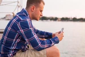 Man sitting on the bridge next to sea with smartphone