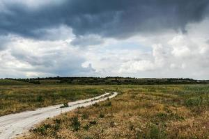 The rural dirt road, beautiful countryside in cloudy weather photo
