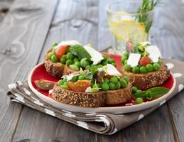 Green peas with cherry tomatoes, feta cheese, mint on toast