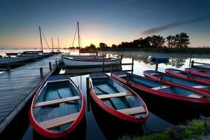 red boats on harbor at sunrise